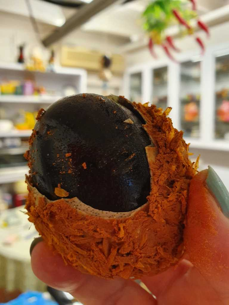 Removing outer husk from Century Egg